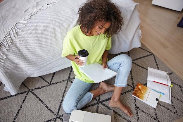 Mooie jonge donkerharige krullende vrouw zittend op een tapijt met geometrische print, koffie drinken en haar huiswerk voorbereiden, het dragen van vrijetijdskleding
