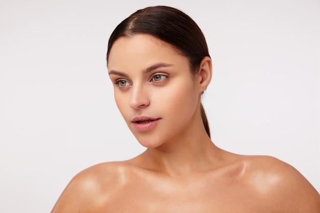 Mooie jonge donkerharige vrouw met natuurlijke make-up dragen paardenstaart kapsel, opzij kijken met open mond, geïsoleerd