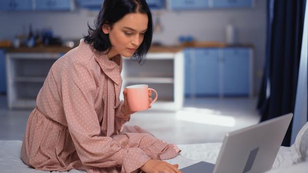 Mooie jonge donkerharige vrouw zittend op het bed met een kopje koffie