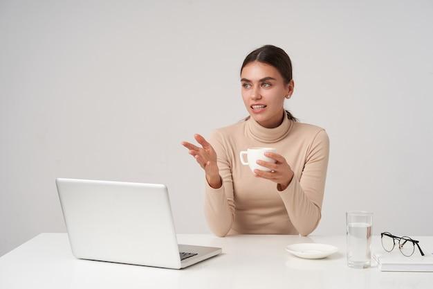 Mooie jonge donkerharige zakelijke dame die een ontmoeting heeft met collega's, een kopje thee houdt terwijl ze over een witte muur in een beige poloneck zit en haar hand omhoog houdt