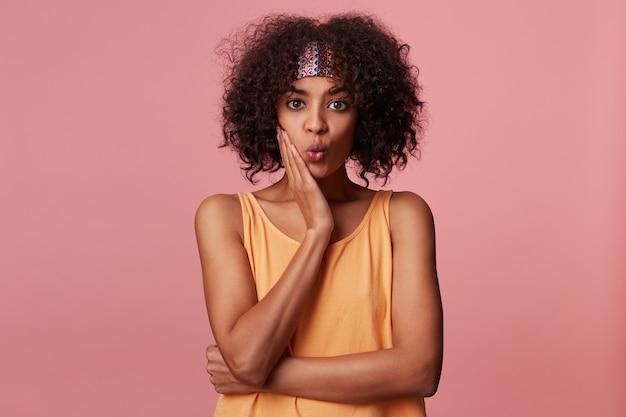 Mooie jonge donkerhuidige brunette vrouw met kort krullend haar met kleurrijke hoofdband en vrijetijdskleding, handpalm op haar gezicht en krullende lippen