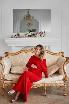 Mooie jonge draagvrouw in modieuze rode avondjurk zit op de gouden vintage bank op luxe interieur versierd met bloemen