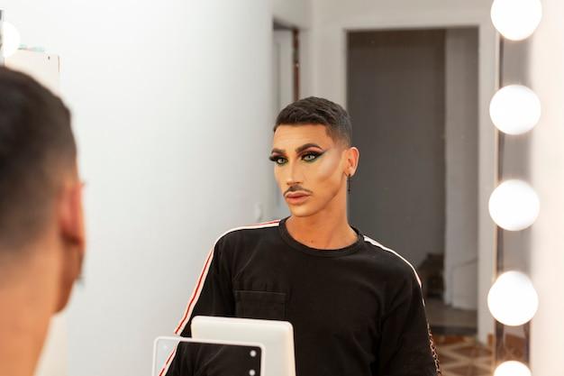 Mooie jonge drag queen visagist kijkt naar zichzelf voor de spiegel
