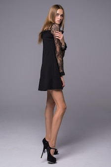 Mooie jonge dunne figuur meisje gekleed in zwarte zijden jurk