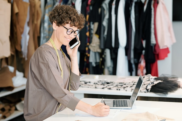 Mooie jonge eigenaar van mode-ontwerpstudio, cliënten raadplegen over smartphone en notities maken