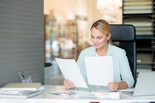 Mooie jonge elegante leraar papieren van studenten lezen terwijl ze door bureau controleren