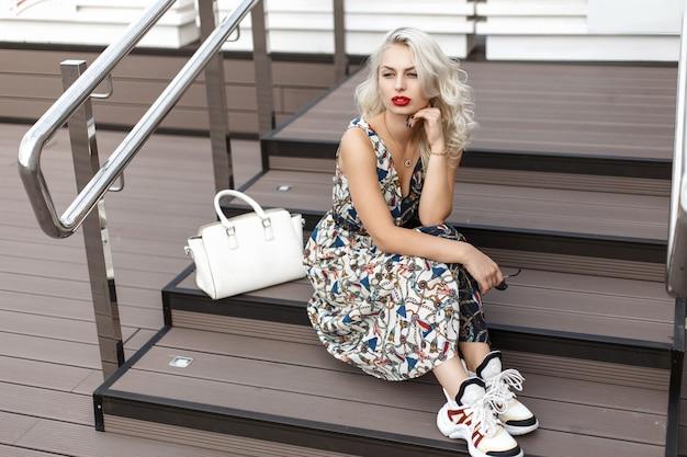 Mooie jonge elegante model vrouw in een mode zomerjurk en sneakers met een witte stijlvolle tas zittend op houten trap