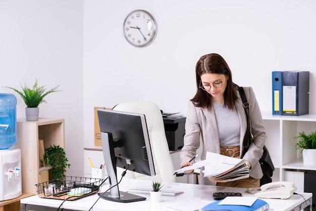 Mooie jonge elegante onderneemster die met handtas op schouder door documenten kijkt terwijl hij over bureau in bureau buigt
