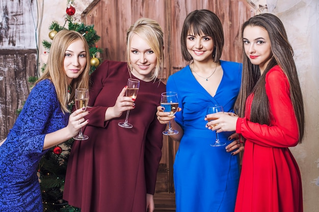 Mooie jonge en gelukkige vrouwelijke vriendinnen samen om kerstmis te vieren