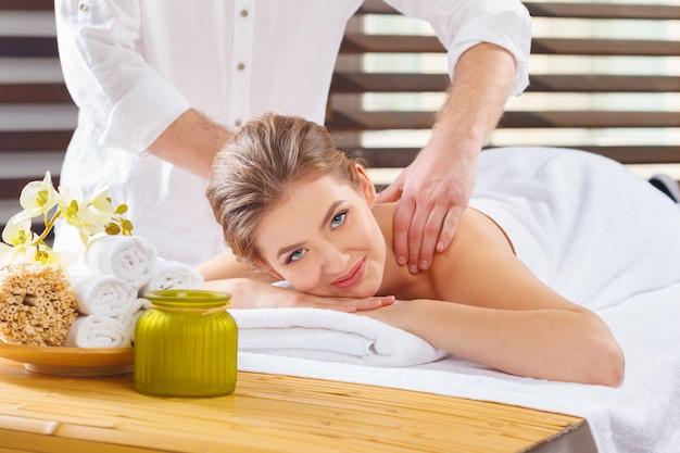 Mooie, jonge en gezonde vrouw in spa salon. massage behandeling