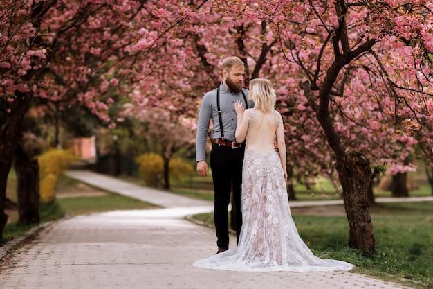 Mooie, jonge en schattige vrouw in luxe jurk en bebaarde hipster man in bloeiende roze kers of sakura tuin, knuffelen en kijken naar elkaar op een zonnige dag. lente bruiloft portret