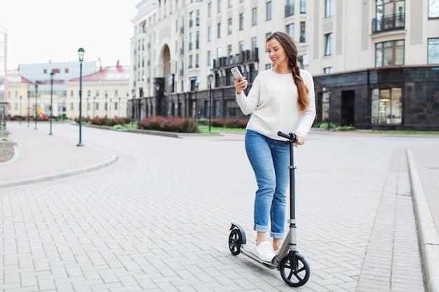 Mooie, jonge en witgetande meid met lang bruin haar stopte tijdens het rijden op de scooter