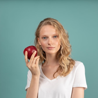 Mooie jonge ernstige slimme blonde vrouw zonder make-up met rode appel