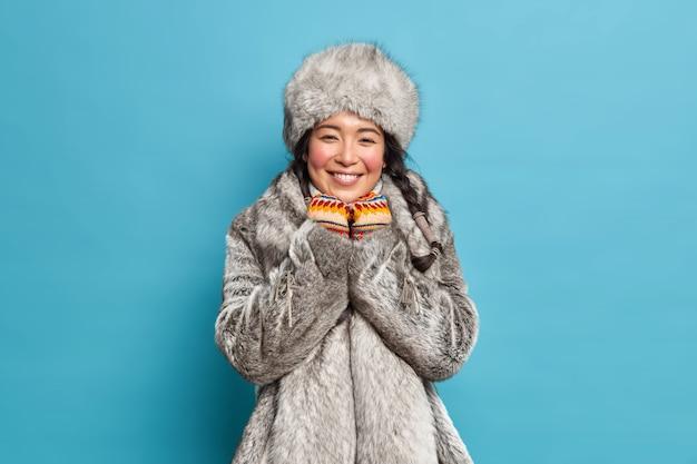 Mooie jonge eskimo-vrouw met rode wangen na tijd doorbrengen bij vorst glimlacht zachtjes heeft twee pigtails draagt bontjas en muts gebreide wanten geïsoleerd over blauwe muur