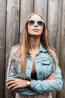 Mooie jonge europese vrouw in modieuze zonnebrillen in een spijkerjasje met kanten zwarte kleding staat in de buurt van een oude houten muur