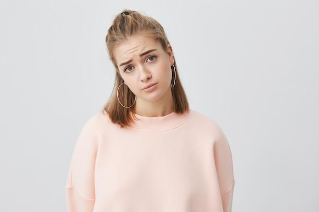 Mooie jonge europese vrouw met blond haar op zoek met ongelukkige en spijtige uitstraling. droevig mooi meisje dat verstoord voelt terwijl het alleen thuis doorbrengen van tijd.