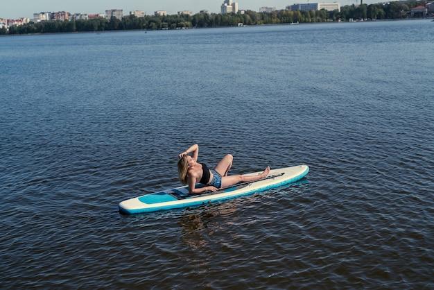 Mooie jonge europese vrouw met sup board op het water van de rivier