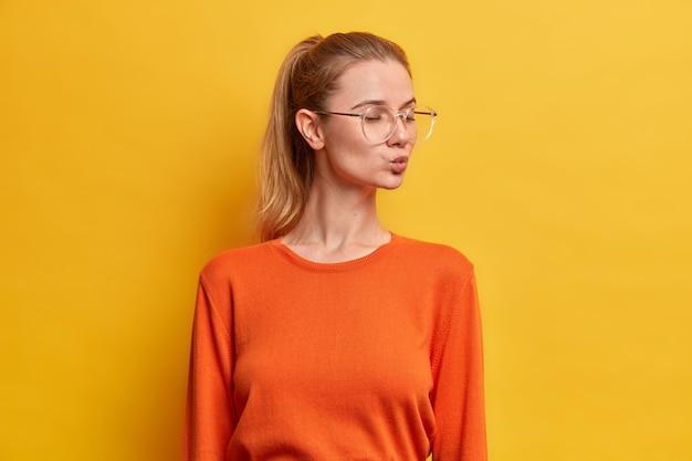 Mooie jonge europese vrouw staat met gesloten ogen, houdt de lippen rond, heeft een romantische bui, paardenstaart, draagt een oranje trui,