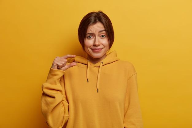Mooie jonge europese vrouw toont klein formaat, toont kleine maat, spreekt over hoeveelheid, gekleed in casual hoodie, vormt een klein voorwerp, geïsoleerd op een gele muur. lichaamstaal concept.