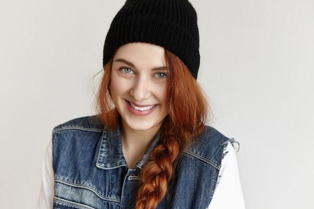 Mooie jonge europese vrouwelijke student met charismatische glimlach die haar gemberhaar in slordige paardenstaart draagt