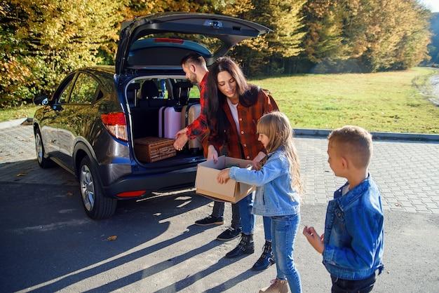 Mooie jonge familie die de auto laadt