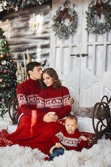 Mooie jonge familie in lelijke truien in versierd kerstinterieur. jonge schattige peuter en zijn ouders in kerstkleren