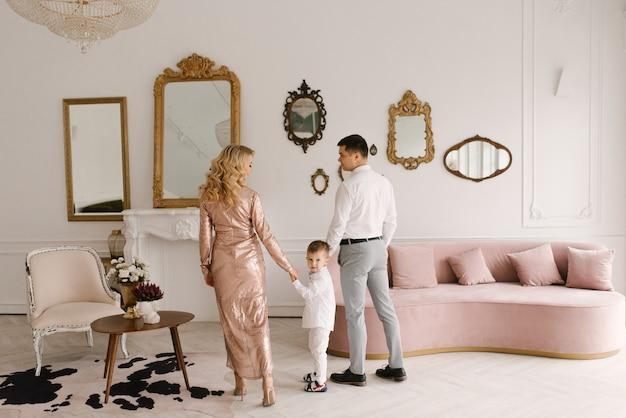 Mooie jonge familie man vrouw en zoon in slimme kleding in een luxe, lichte interieur, gelukkige familie