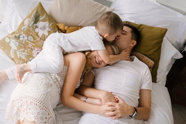 Mooie jonge familie man vrouw en zoon in witte kleren spelen op het bed thuis