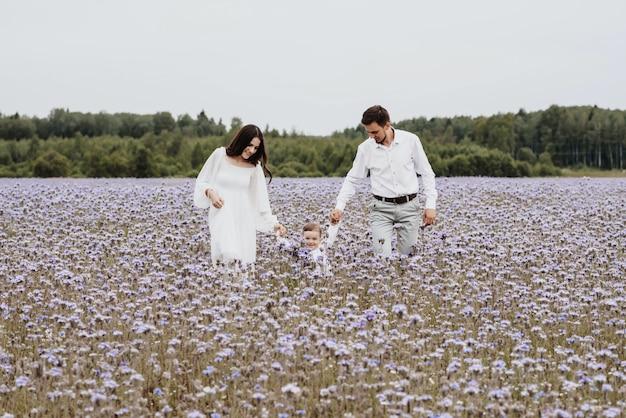 Mooie jonge familie met een jongen die op een gebied van bloemen rust.