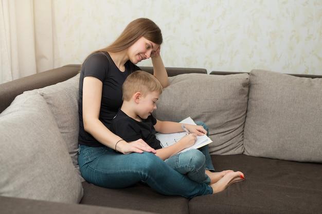 Mooie jonge familie moeder en zoon huiswerklessen