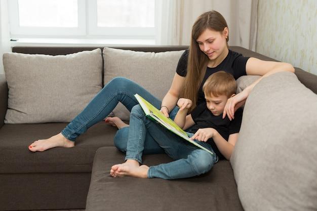 Mooie jonge familie moeder en zoon lezen thuis een boek