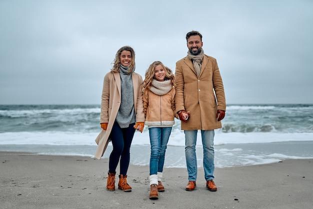 Mooie jonge familie staan aan de kust, hand in hand, warme kleren en sjaals dragen.