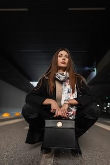 Mooie jonge fashion model stijlvolle vrouw met sjaal in jas in spijkerbroek met lederen zwarte modieuze handtas poseren zittend op de weg in de stad. stedelijk meisje in trendy kleding rust buiten.