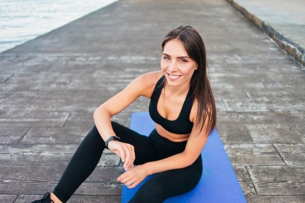 Mooie jonge fit vrouw geniet van slimme armband zittend op de mat op het strand