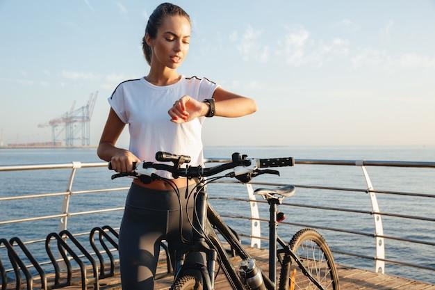 Mooie jonge fitness meisje permanent buiten met een fiets, zee landschap