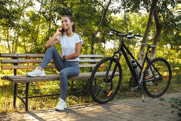 Mooie jonge fitness meisje, zittend op een bankje met fiets in het park