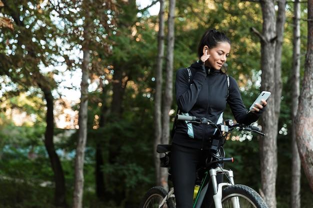 Mooie jonge fitness vrouw rijden op een fiets in het park, luisteren naar muziek met koptelefoon, mobiele telefoon houden