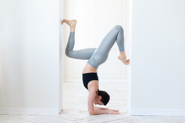 Mooie jonge fitnessblogger die een moeilijke handstand doet op een witte achtergrond binnenshuis