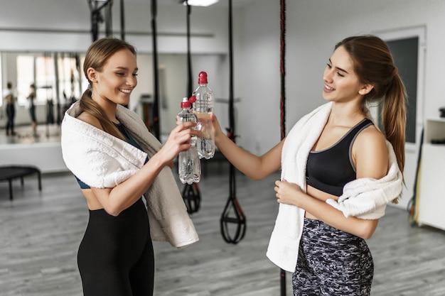 Mooie jonge fitnessmeisjes houden flessen water vast, handdoek op de rug, kijken elkaar aan en glimlachen