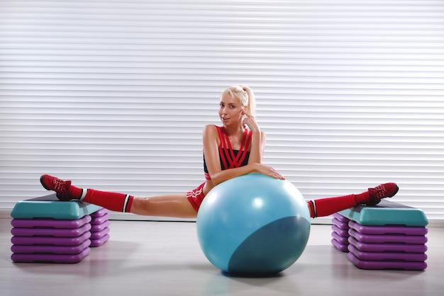 Mooie jonge flexibele geschiktheidsvrouw die spleten doet tijdens haar w