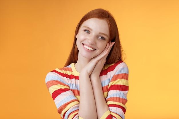 Mooie jonge flirterige roodharige europees meisje glimlachend breed opgewonden gelukkig magere palm ontvangen zoete tedere huidige blik dankbaar geamuseerd vreugdevol reagerend aangenaam moment, staande oranje achtergrond.