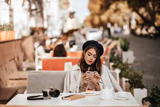 Mooie jonge fotograaf met donkerbruin golvend kapsel, baret, beige trenchcoat zittend op het terras van het stadscafé, thee en cheesecake, vasthouden en kijken naar mobiele telefoon