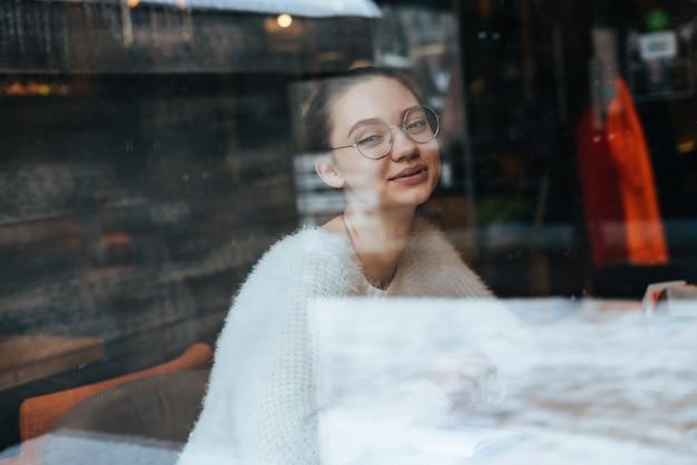 Mooie jonge freelancer meisje in een witte trui en bril zit in een café en glimlacht