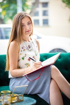 Mooie jonge freelancervrouw die in notitieboekje, bedrijfsmensenconcept schrijven