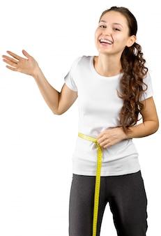 Mooie jonge geïsoleerde vrouw met het meten van band
