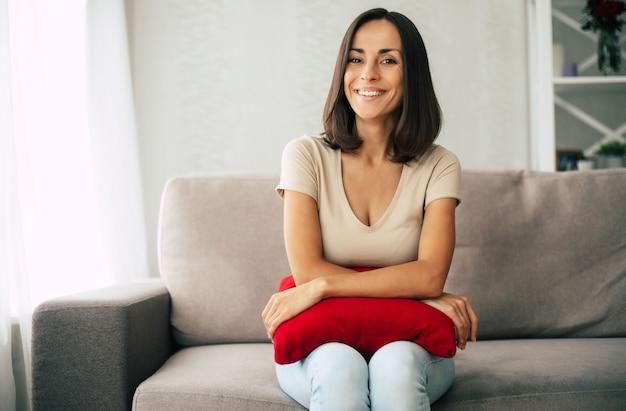 Mooie jonge gelukkig brunette vrouw is thuis ontspannen op de bank en dromen