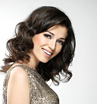 Mooie jonge gelukkig lachende vrouw met bruine krullende haren vormt