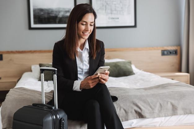 Mooie jonge gelukkig lachende zakenvrouw in formele kleding binnenshuis thuis met koffer met behulp van mobiele telefoon.