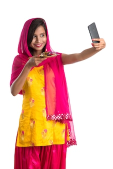 Mooie jonge gelukkig meisje selfie met pooja thali met behulp van een mobiele telefoon of smartphone