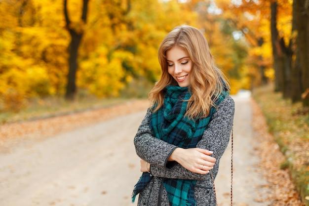 Mooie jonge gelukkig vrouw in stijlvolle jas poseren in herfst park